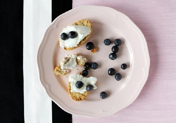 小さく切ったベーグルにクリームチーズとブルーベリーが載っている画像