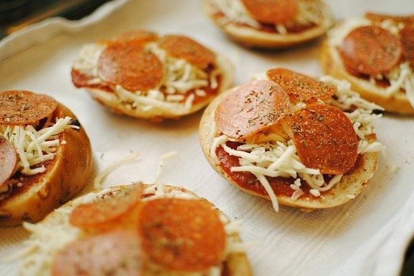 小さくスライスされたベーグルの上に、チーズとサラミが載っている