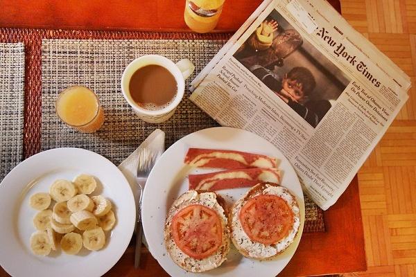 ニューヨーカーの朝食。ベーグル、トマト、ベーコン、バナナ、オレンジジュース、コーヒー。横にはNYタイムス紙がある。