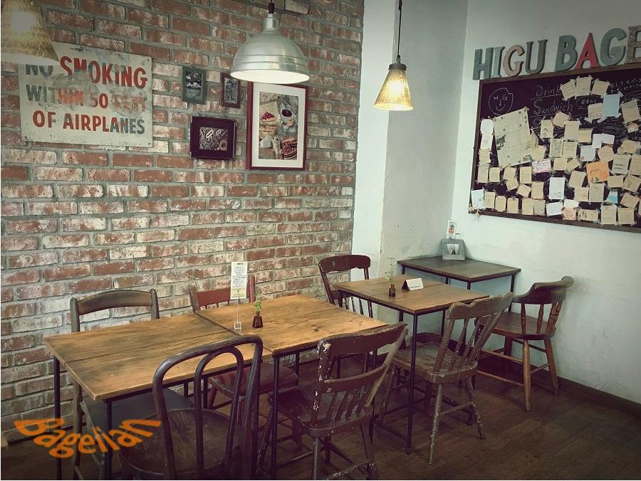 ヒグベーグル&カフェの店内。レンガ作りの壁の前に、古いイスとテーブルが並んでいる。