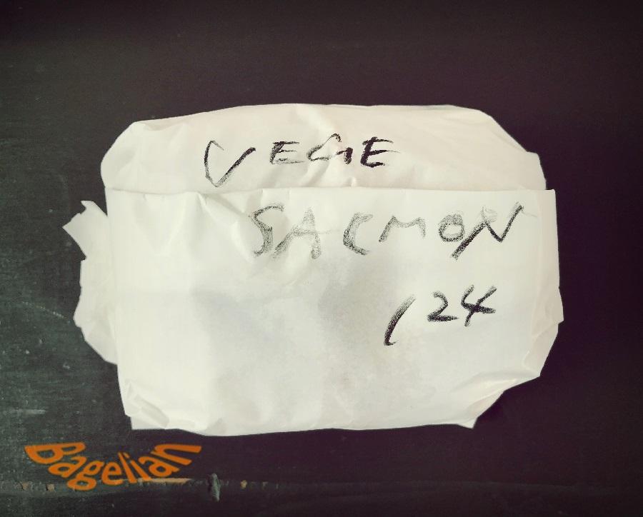 白い紙にくるまれたベーグルサンド。手書きでVege, Sarmon, 124と書かれている